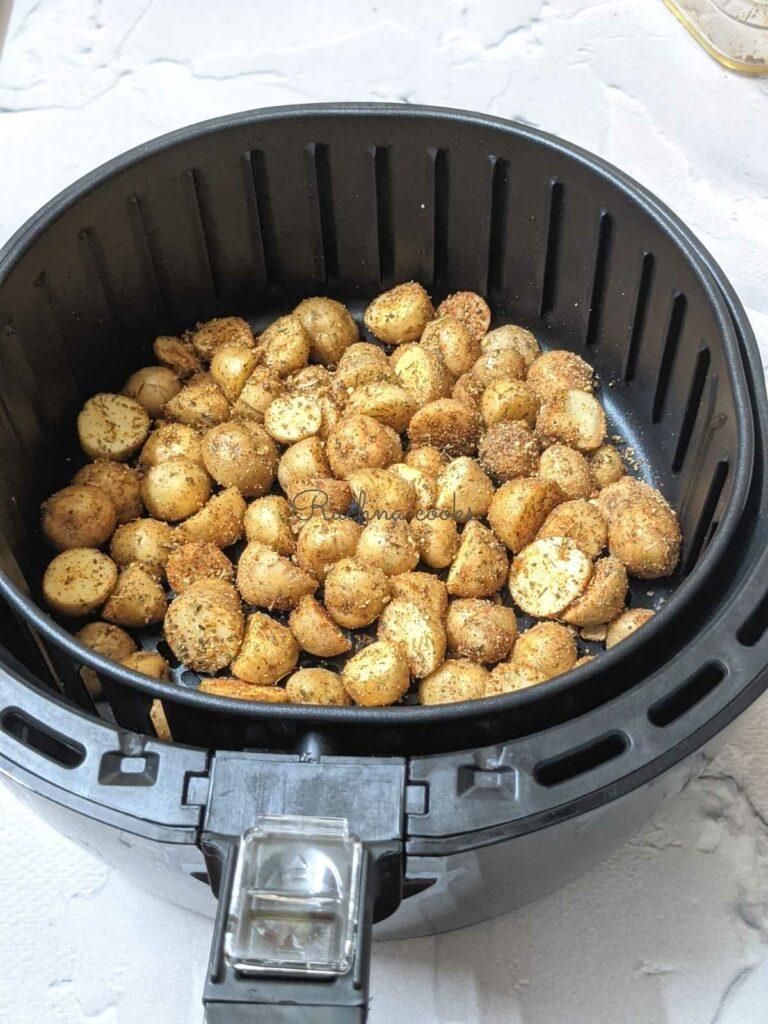 Coated baby poatoes in air fryer basket