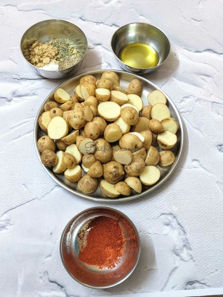 Baby potatoes cut in halves in a plate, with bowls of olive oil, spices and paprika.