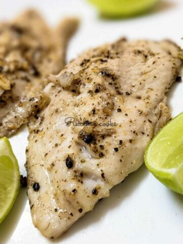 Air fryer tilapia fillet in closeup with lemon wedges on a white plate